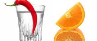 Стакан с водкой и перцем рядом долька апельсина